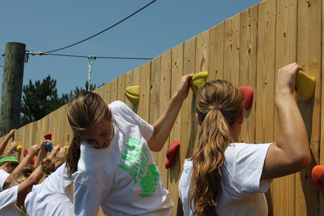 An athletic team navigates the climbing wall challenge.